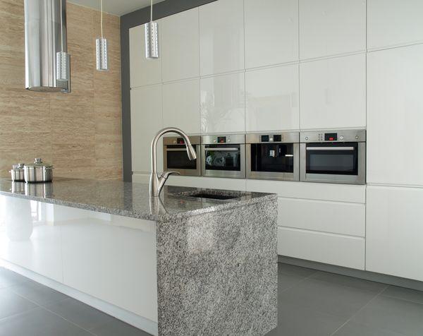Modern minimalist white kitchen with grey granite countertop